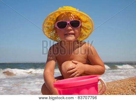 Adorable toddler girl playing with toys on sand beach