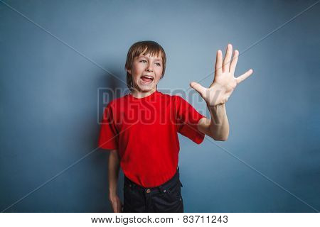 Boy, teenager, twelve years old, in a red shirt, showing a hand