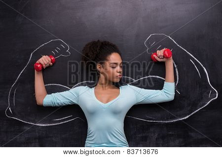 Afro-american woman with dumbbells and painted muscular arms on chalkboard