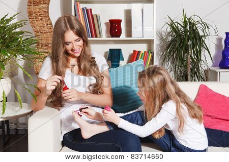 Mother And Little Daughter painting their nails and toes