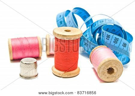 Meter, Thimble And Spools Of Thread On White