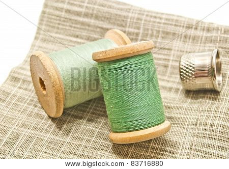 Two Spools Of Green Thread On Fabric