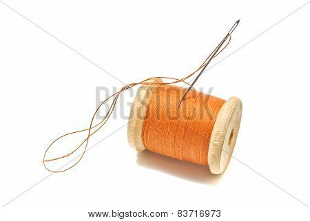 Spool Of Orange Thread And Needle