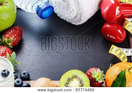 Fitness Frame With Dumbbells, Towel And Fresh Fruits