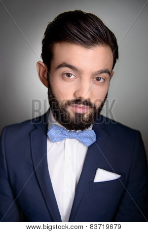 Stylish man with beard and bow tie looking at camera