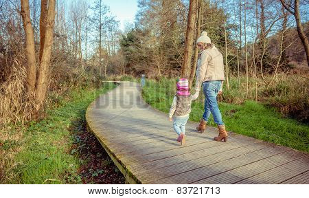 Mother and daughter walking together holding hands