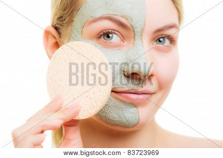 Woman removing green clay mud facial mask with sponge isolated on white.