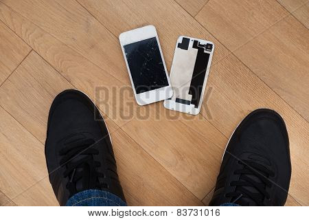 Person Standing Near Broken Cellphone