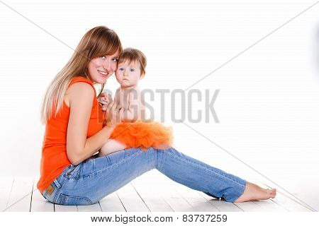 Portrait of a happy young mother holding baby girl, cute family at home, loving mom