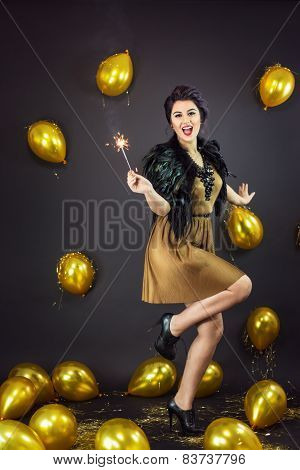 Happy Fashion Woman Dancing, Holding Fireworks Dressed In A Gold Dress And Feathers Collar, Surround