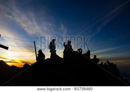 Hikers On Top Of Mountain At Sunrise / Sunset