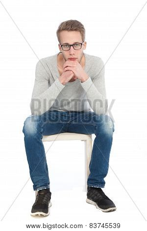 Thoughtful Young Man In Glasses On A Chair