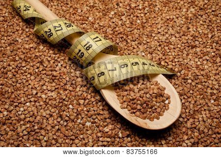Centimeter Tape Over Wooden Spoon On Buckwheat Background