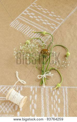 Still life with garlic, buds, flowers and spool of twine