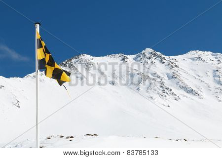 Yellow And Black Avalanche Risk Warning Flag Flying In The Mountains.