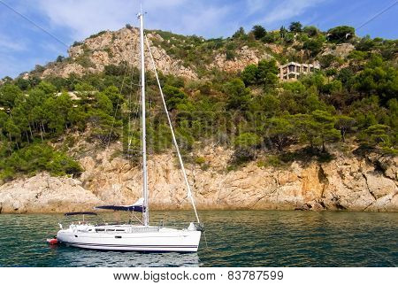 A Sailing Boat Near The Coastline Of Costa Brava, In Spain