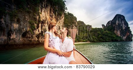 Bride Look At Groom Sitting On Longtail Boat