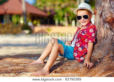 Portrait Of Smiling Boy Sitting Under The Tree