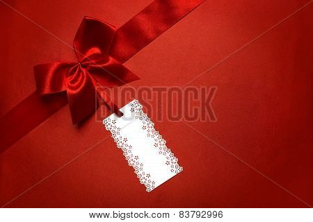 Red Silk Cloth Background With Tag Label And Ribbon Bow, Present Pricing Tag Over Fabric Texture