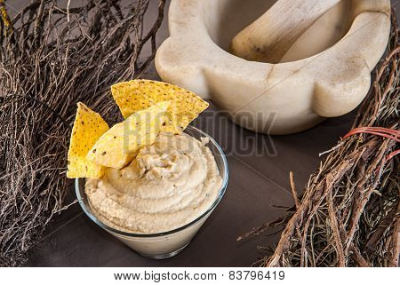 bowl of hummus with decor and kitchen mortar