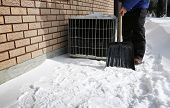 picture of shovel  - Man shoveling the show with brick wall and air conditioner on background - JPG
