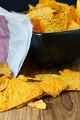 image of nachos  - Nacho cheese flavored tortilla chips in a dark bowl on a wooden table.