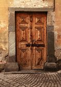 image of stone house  - Vintage brown wood medieval door in rural stone wall house - JPG