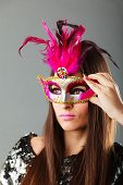 stock photo of venetian carnival  - Closeup woman face with carnival venetian mask on gray background - JPG