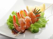 picture of leek  - Roasted shrimps on the skewer with fresh green lettuce leek rosemary lemon and soy sauce on the white plate - JPG