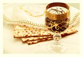 foto of hebrew  - the symbols of the feast of Passover three pieces of matzah poured a glass of red wine white cloth with embroidery and font on the Hebrew Pesach on a white background isolated - JPG