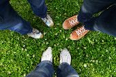 stock photo of adults only  - Group of friends standing in a circle on a spring meadow but only their feet in sneakers is visible - JPG
