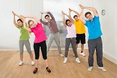 stock photo of  practices  - Group Of Happy Multiethnic People Practicing Yoga - JPG