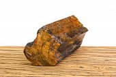 picture of petrified  - Brown piece of petrified wood on old oak surface white background - JPG
