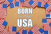 stock photo of born  - Miniature flags of the United States of America form a border on brown card around the phrase Born in the USA - JPG