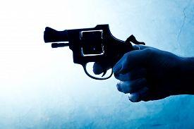 stock photo of gunshot  - Silhouette of a mans hand with a handgun in blue - JPG
