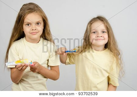 The Girl Squeezes Out A Tube Of Toothpaste On The Brush