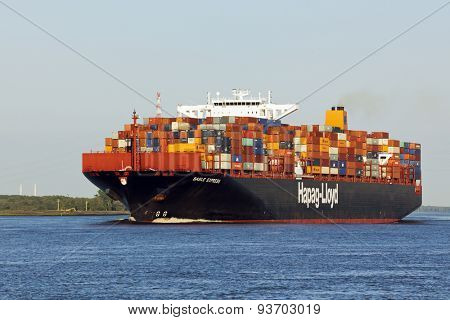 Stade, Germany - June 11, 2015: Container ship Basle Express on the Elbe river near Stade. The Post-Panamax-Class ship is owned and operated by Hapag-Lloyd, port of registry is Hamburg.