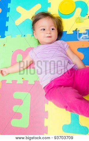 Adorable baby girl lying on floor mats