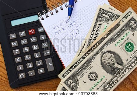 Calculator, money, notebook with calculations, pen on the table.