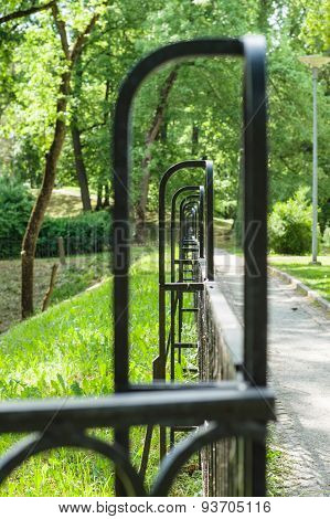 Abstract Vanishing Decorative Wrought Iron Fence In Summer Park