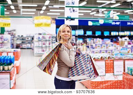 Happy Woman With Packages For Purchases In Store