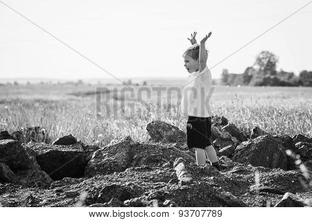 Little boy in a field of tall grass. Kid playing, running in nature.