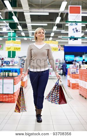 Happy Woman Walks With Shopping Bags On Store