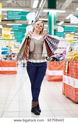 Happy Woman Standing With Shopping Bags On Store