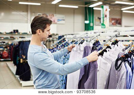 Man Chooses Shirt In Store