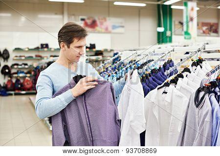 Man Chooses A Shirt In Shop