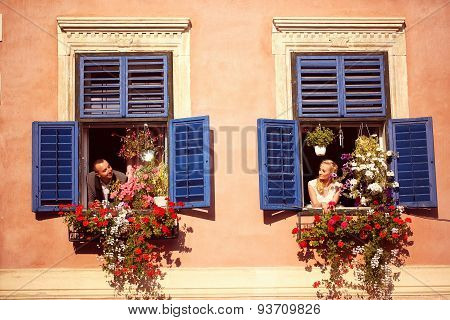 Bride And Groom Having Fun From Window Of Old House