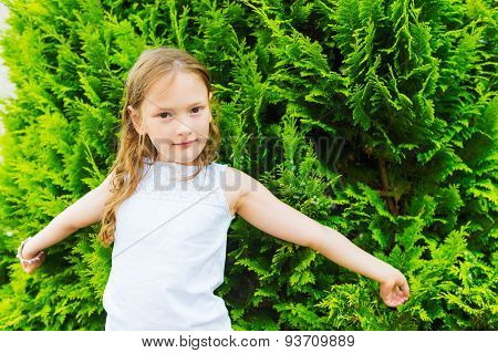 Outdoor portrait of a cute little girl wearing white shirt, arms wide open