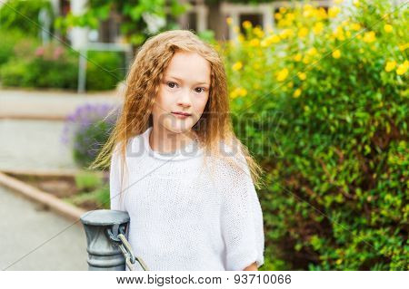 Outdoor portrait of a cute little girl of 7 years old, wearing white knitted pullover