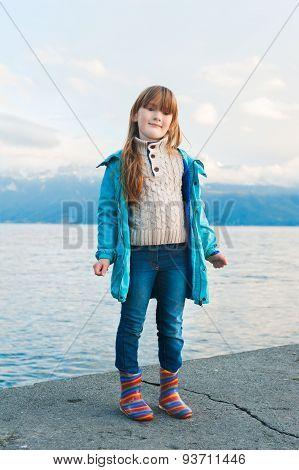 Outdoor portrait of a cute little girl resting by the lkae, wearing blue coat